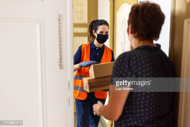woman making courier delivery during pandemic - receiving stock pictures, royalty-free photos & images