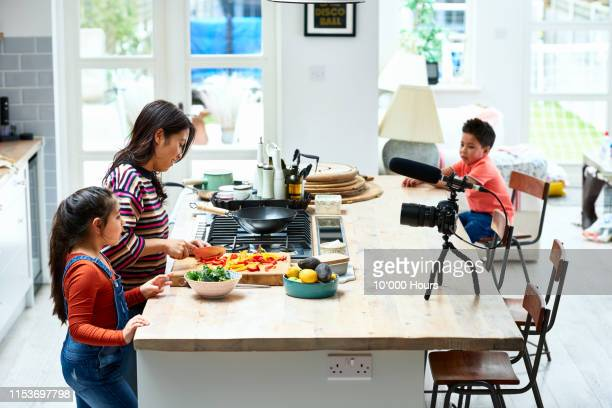 woman making dinner with son and daughter in kitchen - filipino family dinner stock pictures, royalty-free photos & images