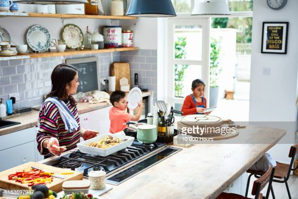woman making dinner with two children helping to set table - filipino family dinner stock pictures, royalty-free photos & images