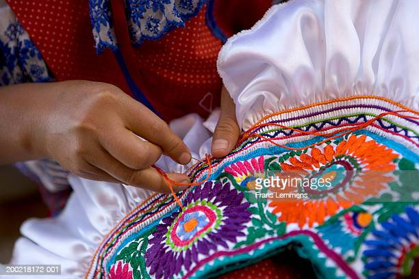 Woman making embroidery on skirt, close-up