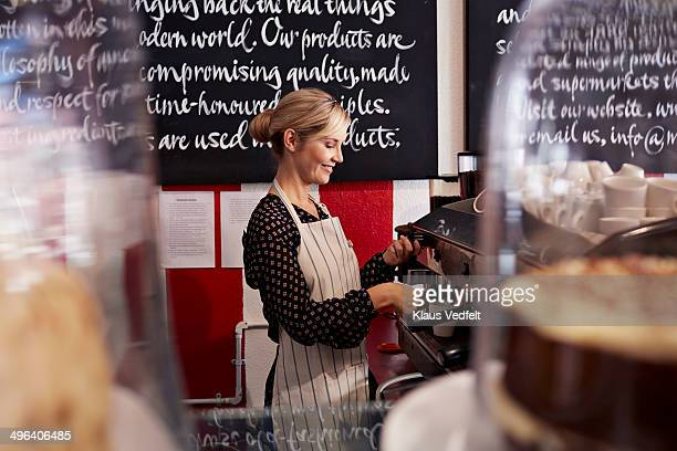 Woman making Espresso at cafe