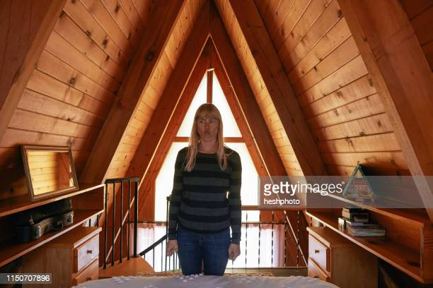 woman making face in bedroom in a-frame house - heshphoto stock pictures, royalty-free photos & images