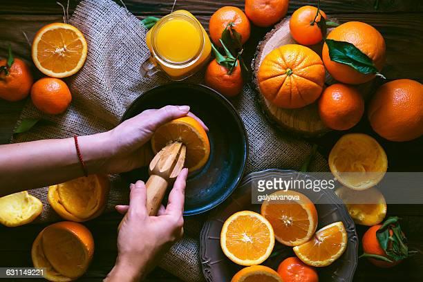 Woman making freshly squeezed orange juice