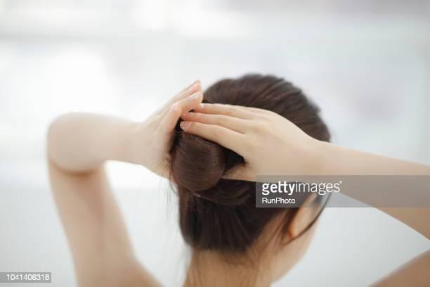 woman making hair bun - hair bun stock pictures, royalty-free photos & images