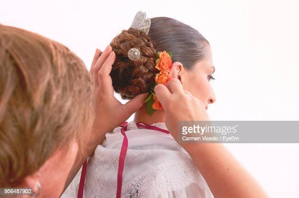 Woman Making Hairstyle Of Bride Against White Background