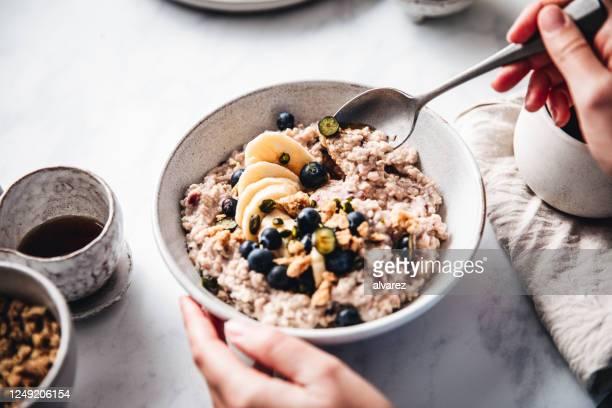 vrouw die gezond ontbijt in keuken maakt - ontbijt stockfoto's en -beelden