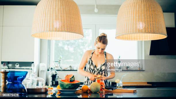 woman making healthy meal from melon and watermelon in the kitchen - nutritionist stock pictures, royalty-free photos & images