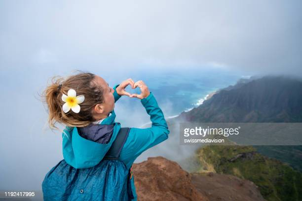 woman making heart frame on spectacular landscape in hawaii from mountain top - kauai stock pictures, royalty-free photos & images