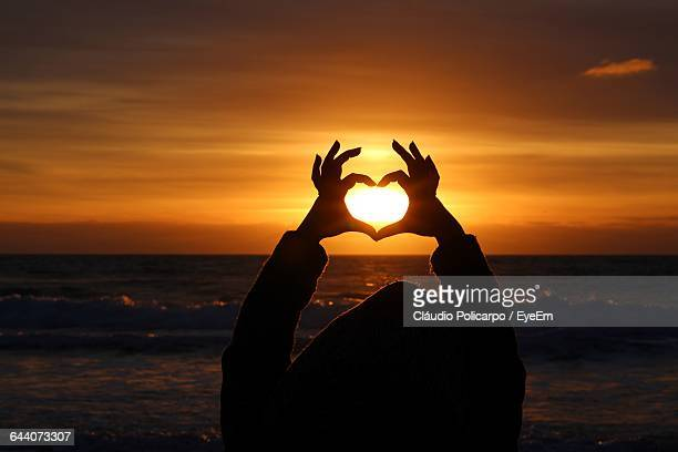 Woman Making Heart Shape Amidst Sea At Beach During Sunset
