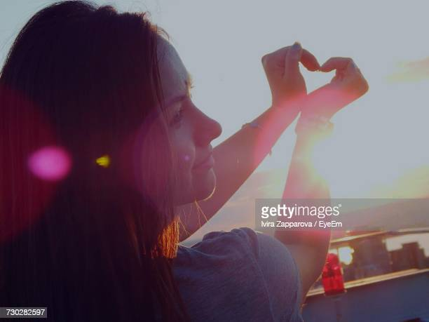 Woman Making Heart Shape Using Hand Against Sky During Sunset