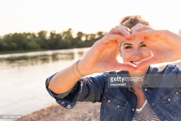woman making heart shape with hands and fingers - heart shape stock pictures, royalty-free photos & images