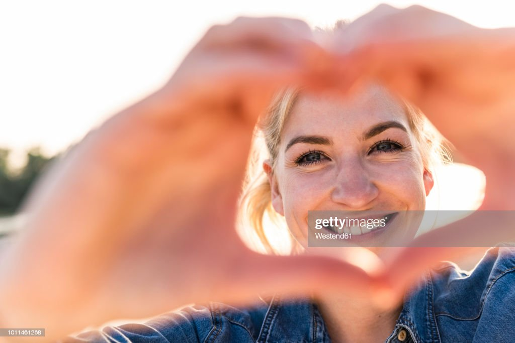 Woman making heart shape with hands and fingers : Stock Photo