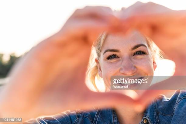 woman making heart shape with hands and fingers - love emotion stockfoto's en -beelden