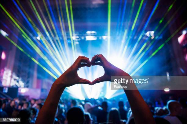 woman making heart shape with hands at music event - konzert stock-fotos und bilder