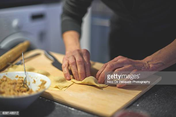 woman making homemade ravioli - スタッフィング ストックフォトと画像