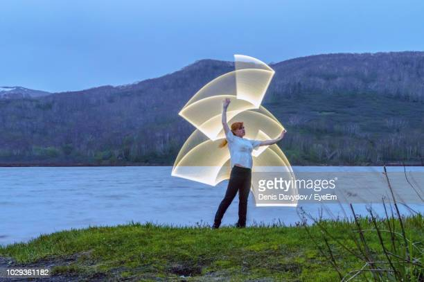 woman making lighting paintings by lake - lichtmalerei stock-fotos und bilder