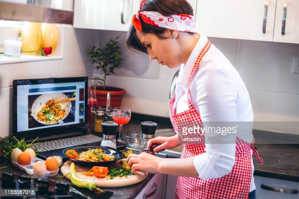 woman making meal with tutorial - youtube stock pictures, royalty-free photos & images