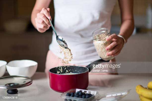 woman making morning breakfast oatmeal cereals and adding ingredients at home - buckwheat stock pictures, royalty-free photos & images