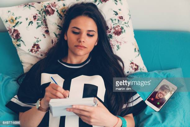 Woman making notes in bed