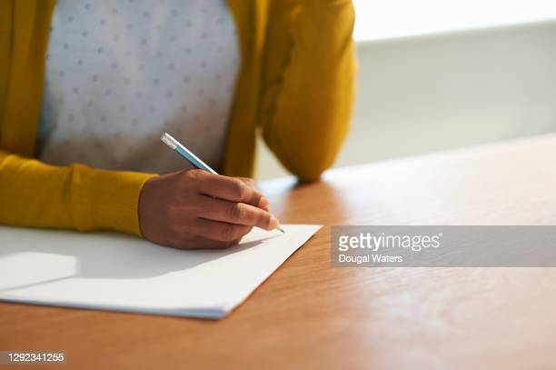 woman making notes with pencil and paper close up. - message stock pictures, royalty-free photos & images