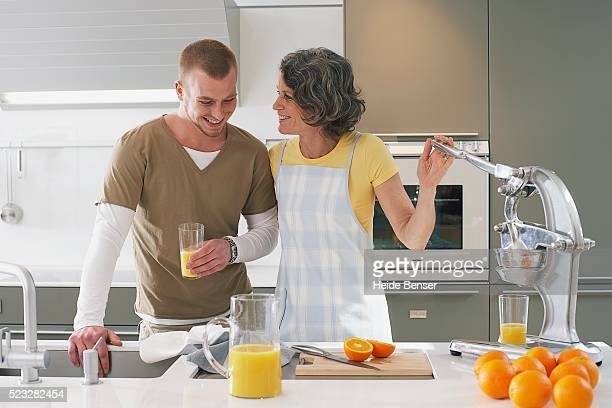 Woman making orange juice for son