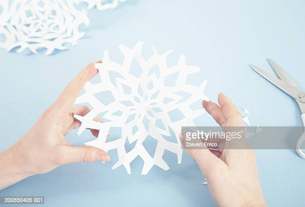 Woman making paper snowflakes, close-up of hands