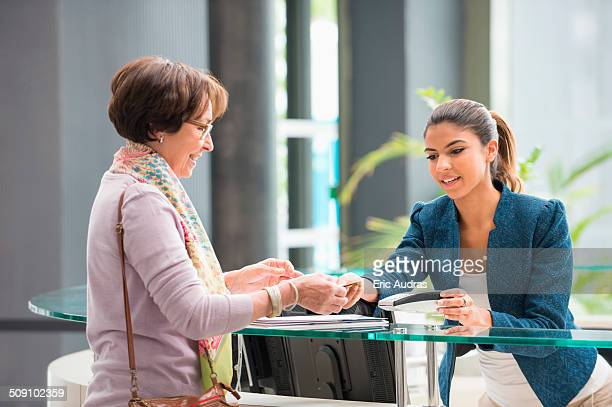 Woman making payment with credit card at reception desk