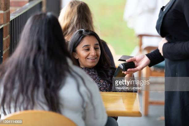 woman making payment with credit card in cafe - disabilitycollection stock-fotos und bilder