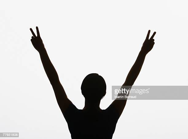 Woman making peace signs with both hands in air