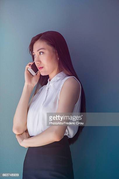woman making phone call with smartphone - sleeveless stock pictures, royalty-free photos & images