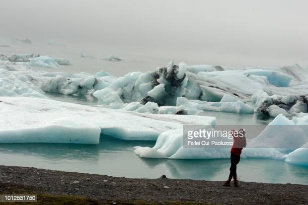 a woman making photo at jökulsárlón lagoon, east iceland - austurland stock-fotos und bilder