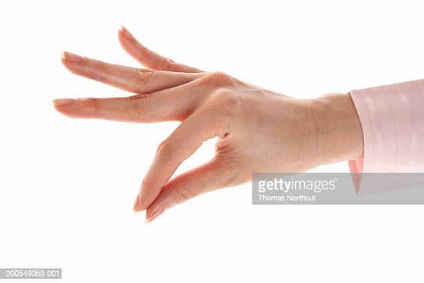 Woman making pinching gesture, close-up of hand