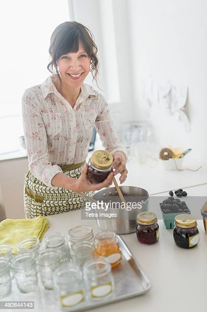 Woman making preserves in kitchen, Jersey City, New Jersey, USA