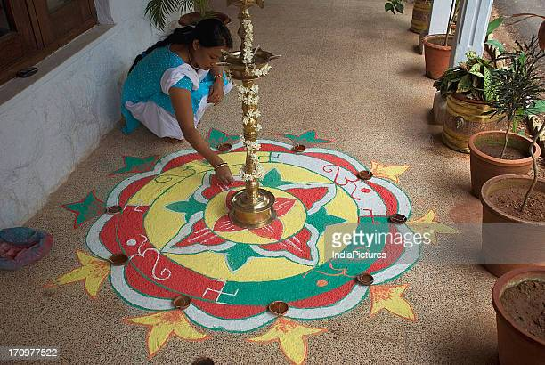 Woman making rangoli during Onam Festival Kerala India