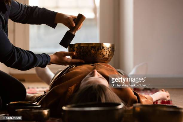 woman making relaxing massage, meditation, sound therapy with tibetian singing bowls. stress relief - rin gong stock pictures, royalty-free photos & images