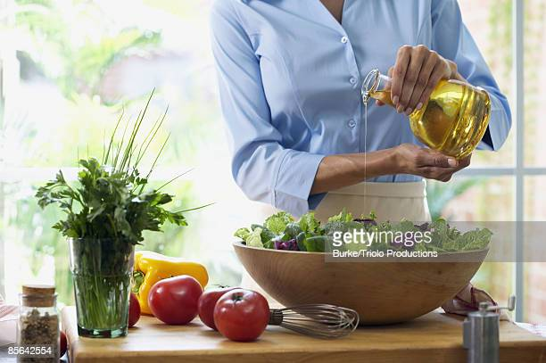 Woman making salad with dressing