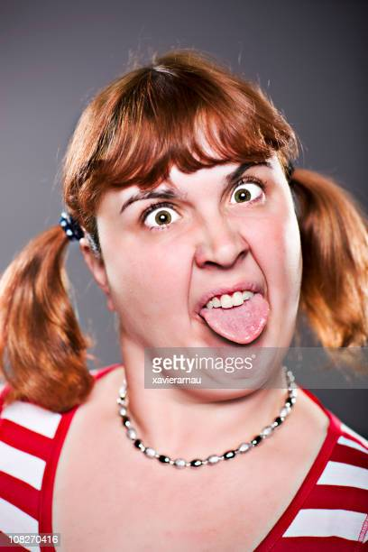 woman making silly face sticking out tongue - dyed red hair stock pictures, royalty-free photos & images