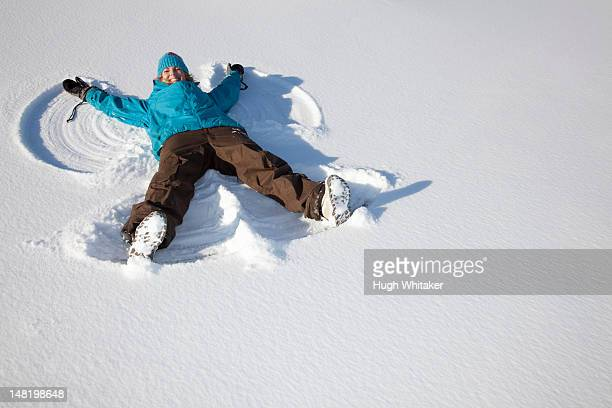 Woman making snow angel on field
