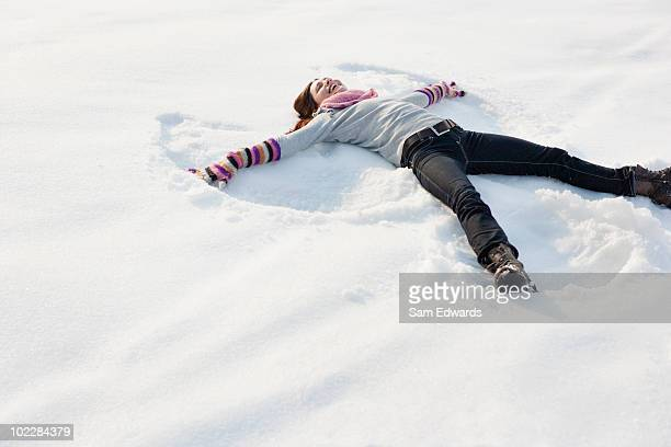 woman making snow angel - snow angel stock photos and pictures