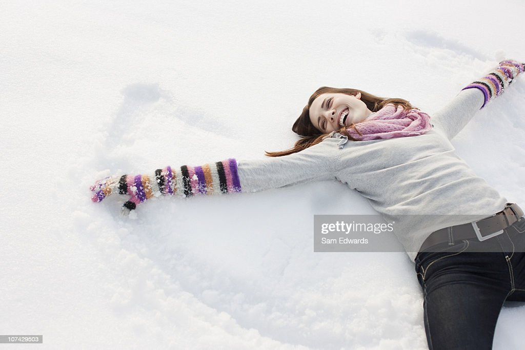 Woman making snow angel : Stock Photo