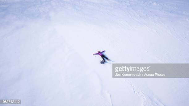 woman making snow angel - wide shot stock pictures, royalty-free photos & images