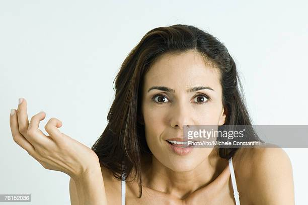 'Woman making surprised face, holding up hand, portrait'