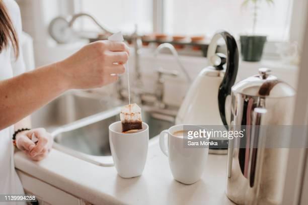 woman making tea in kitchen - やかん ストックフォトと画像