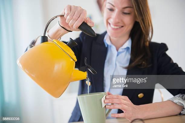 Woman making tea in office