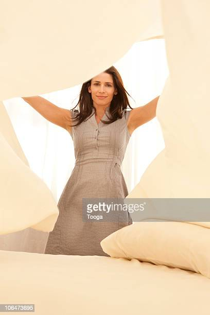 Woman making the bed tossing bed sheets