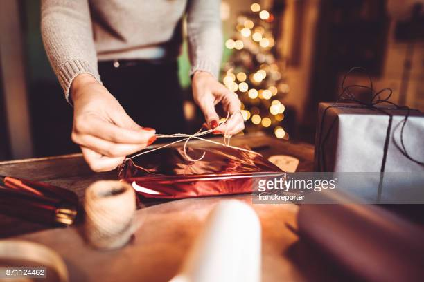 woman making the package for the christmas gift - giving stock photos and pictures