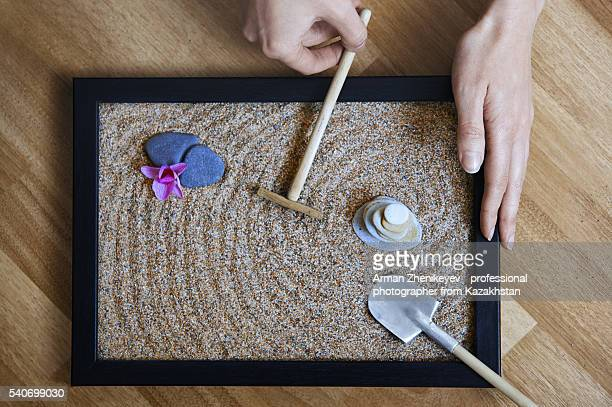Woman making traditional rock garden in a tray