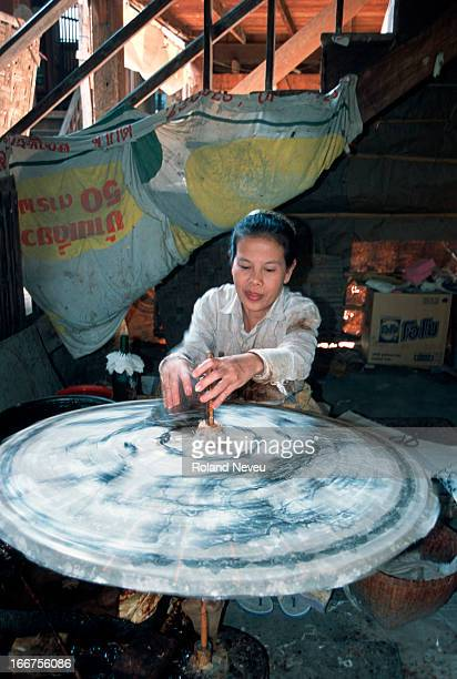 Woman making traditional umbrellas near Chiang Mai, Thailand. These umbrellas are usually made by old people..