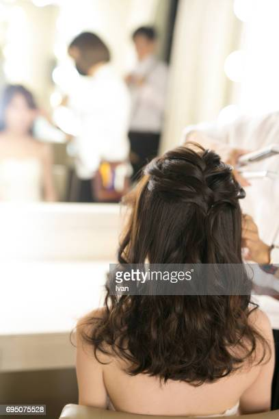 A Woman Making up by a Make-up Artist in front of a Mirror