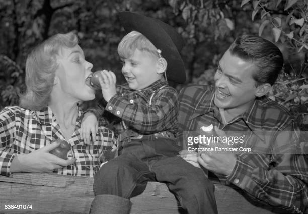 blond boy cowboy hat feeding apple